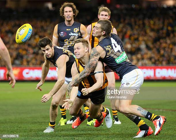 Sam Mitchell of the Hawks handballs whilst being tackled by Dustin Martin of the Tigers during the round 18 AFL match between the Hawthorn Hawks and...