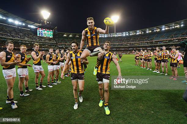 Sam Mitchell of the Hawks is carried off by Jordan Lewis amd Luke Hodge after winning his 300th match during the round 18 AFL match between the...