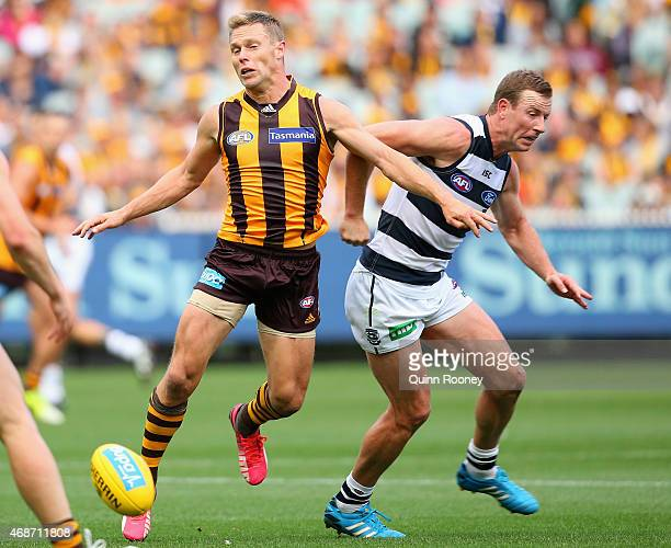 Sam Mitchell of the Hawks is elbowed by Steve Johnson of the Cats during the round one AFL match between the Hawthorn Hawks and the Geelong Cats at...