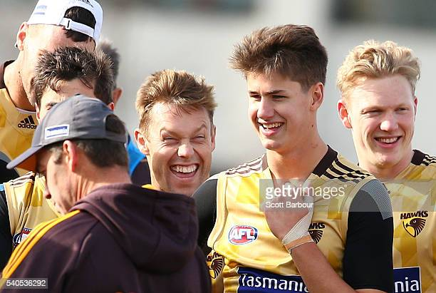 Sam Mitchell of the Hawks laughs as Alastair Clarkson coach of the Hawks speaks and Daniel Howe and James Sicily of the Hawks look on during a...