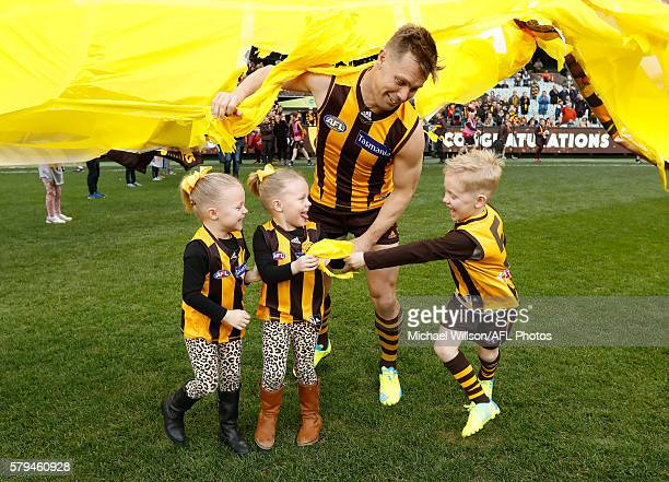 Sam Mitchell of the Hawks runs through the banner with his children for his 300th match during the 2016 AFL Round 18 match between the Hawthorn Hawks...