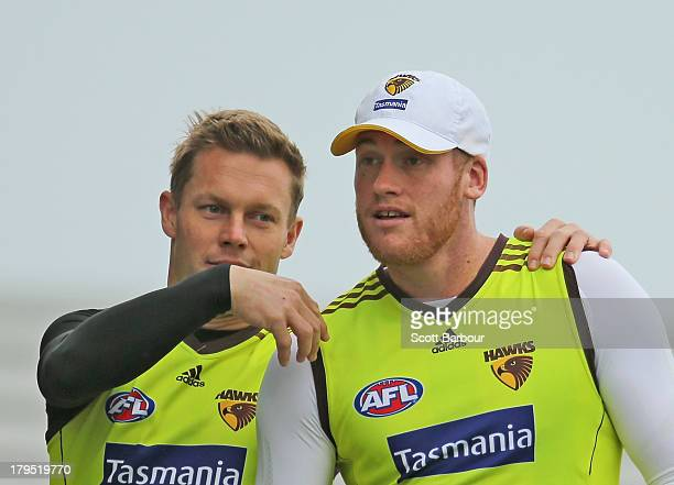 Sam Mitchell puts his arms around Jarryd Roughead of the Hawks during a Hawthorn Hawks AFL training session at Waverley Park on September 5 2013 in...