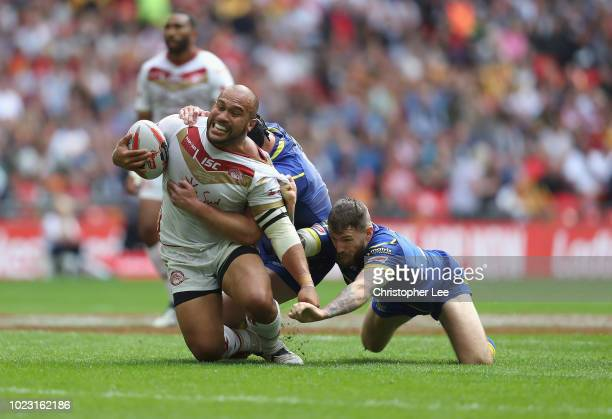 Sam Moa of Catalans Dragons is tackled by Chris Hill and Daryl Clark of Warrington Wolves during the Ladbrokes Challenge Cup Final match between...