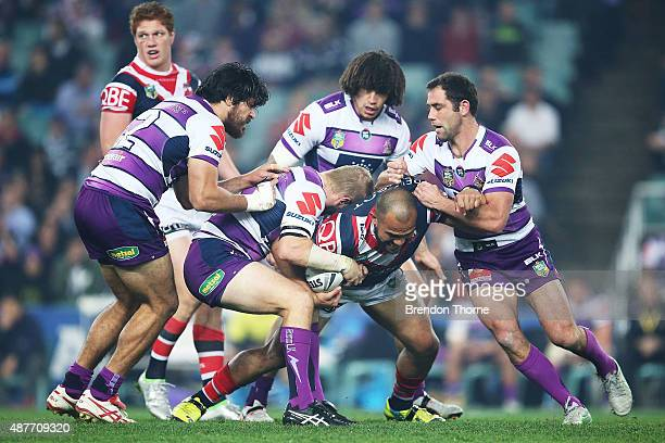 Sam Moa of the Roosters is tackled by by Storm defence during the NRL qualifying final match between the Sydney Roosters and the Melbourne Storm at...