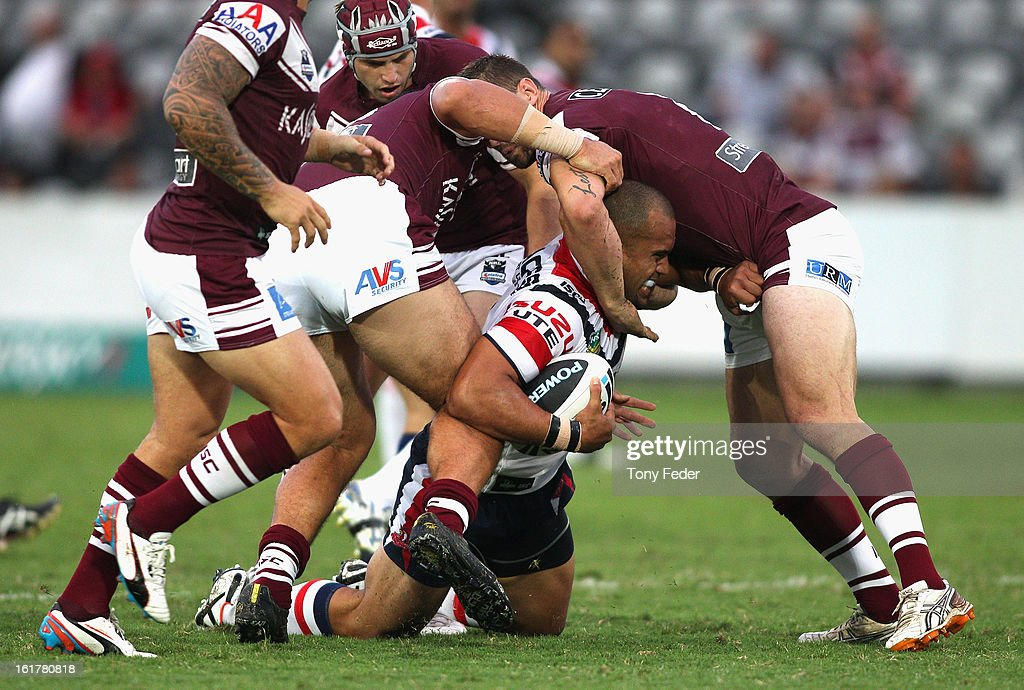 Sam Moa of the Roosters is tackled by Manly defence during the NRL trial match between the Manly Sea Eagles and the Sydney Roosters at Bluetongue Stadium on February 16, 2013 in Gosford, Australia.