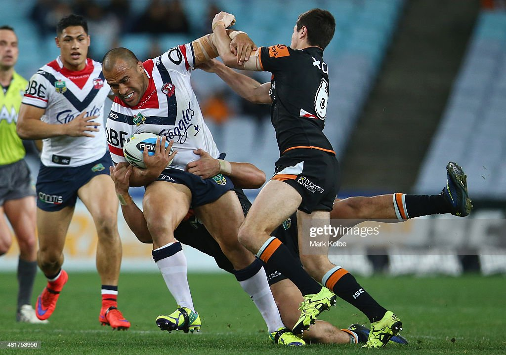 Sam Moa of the Roosters is tackled during the round 20 NRL match between the Wests Tigers and the Sydney Roosters at ANZ Stadium on July 24, 2015 in Sydney, Australia.