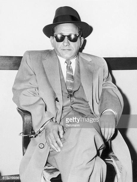Sam 'Mooney' Giancana is handcuffed to a chair in a detective bureau after his arrest Giancana a syndicate gambling boss is being questioned in...
