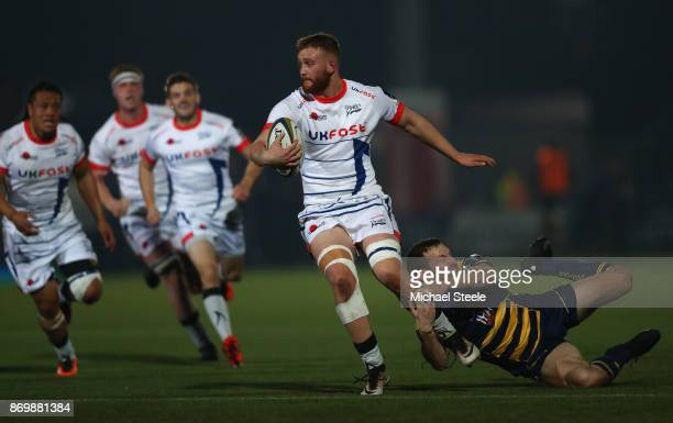 Sam Moore of Sale evades the challenge from Max Stelling of Worcester during the AngloWelsh Cup match between Worcester Warriors and Sale Sharks at...