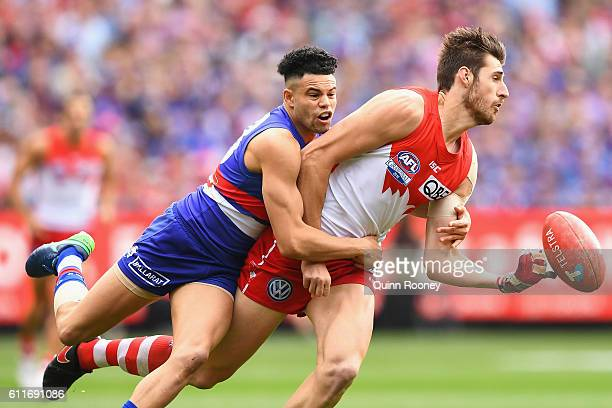 Sam Naismith of the Swans handballs whilst being tackled by Jason Johannisen of the Bulldogs during the 2016 AFL Grand Final match between the Sydney...
