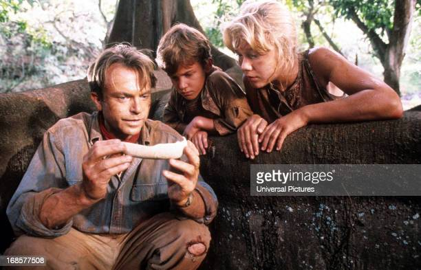 Sam Neill shows a bone to Joseph Mazzello and Ariana Richards in a scene from the film 'Jurassic Park' 1993