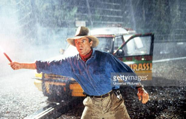 Sam Neill stands out in the rain in a scene from the film 'Jurassic Park', 1993.
