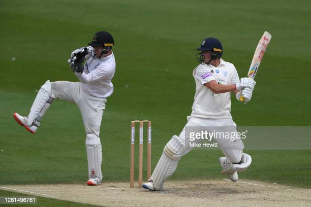 Sam Northeast of Hampshire hits out as wicketkeeper Ben Brown of Sussex looks on during a friendly match between Sussex and Hampshire at County...