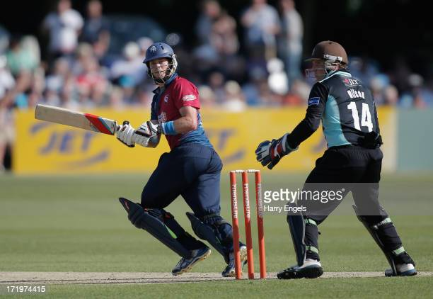 Sam Northeast of Kent hits out as Surrey wicketkeeper Gary Wilson looks on during the Friends Life T20 match between Kent and Surrey at the St...