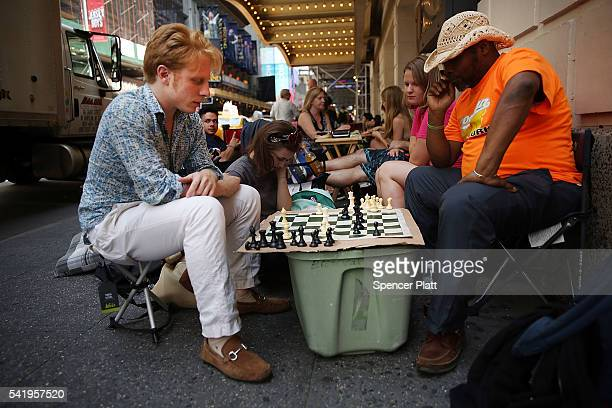 Sam Oliver joins a friend in a game of chess while waiting in line with dozens of others for tickets for the popular Broadway show Hamilton on June...