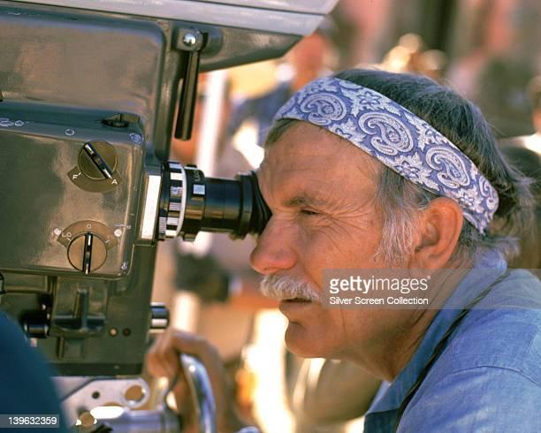 Sam Peckinpah US film director wearing a paisley pattern bandana as he puts his eye to a movie camera during filming circa 1980