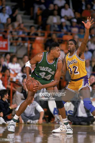 Sam Perkins of the Dallas Mavericks looks to move the ball around the defense of Magic Johnson of the Los Angeles Lakers during the NBA game at the...