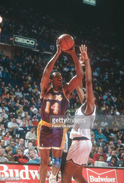 Sam Perkins of the Los Angeles Lakers goes up to shoots over Charles Jones of the Washington Bullets during an NBA basketball game circa 1991 at the...