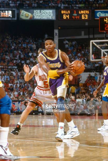 Sam Perkins of the Los Angeles Lakers looks to pass the ball against the Chicago Bulls during an NBA basketball game circa 1990 at the Chicago...