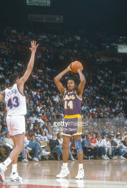 Sam Perkins of the Los Angeles Lakers looks to pass the ball against the Washington Bullets during an NBA basketball game circa 1991 at the Capital...