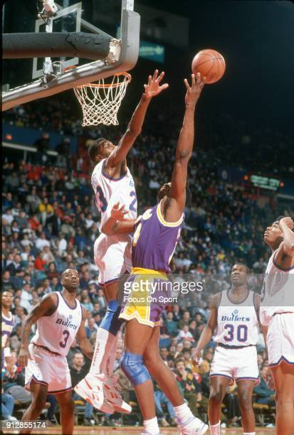 Sam Perkins of the Los Angeles Lakers shoots over Charles Jones of the Washington Bullets during an NBA basketball game circa 1991 at the Capital...