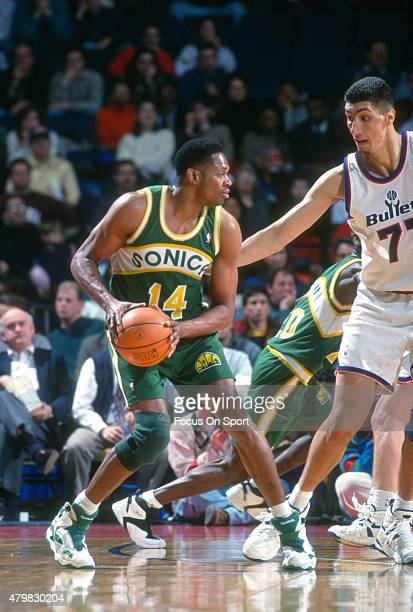 Sam Perkins of the Seattle Super Sonics looks to put a move on Gheorghe Muresan of the Washington Bullets during an NBA basketball game circa 1994 at...