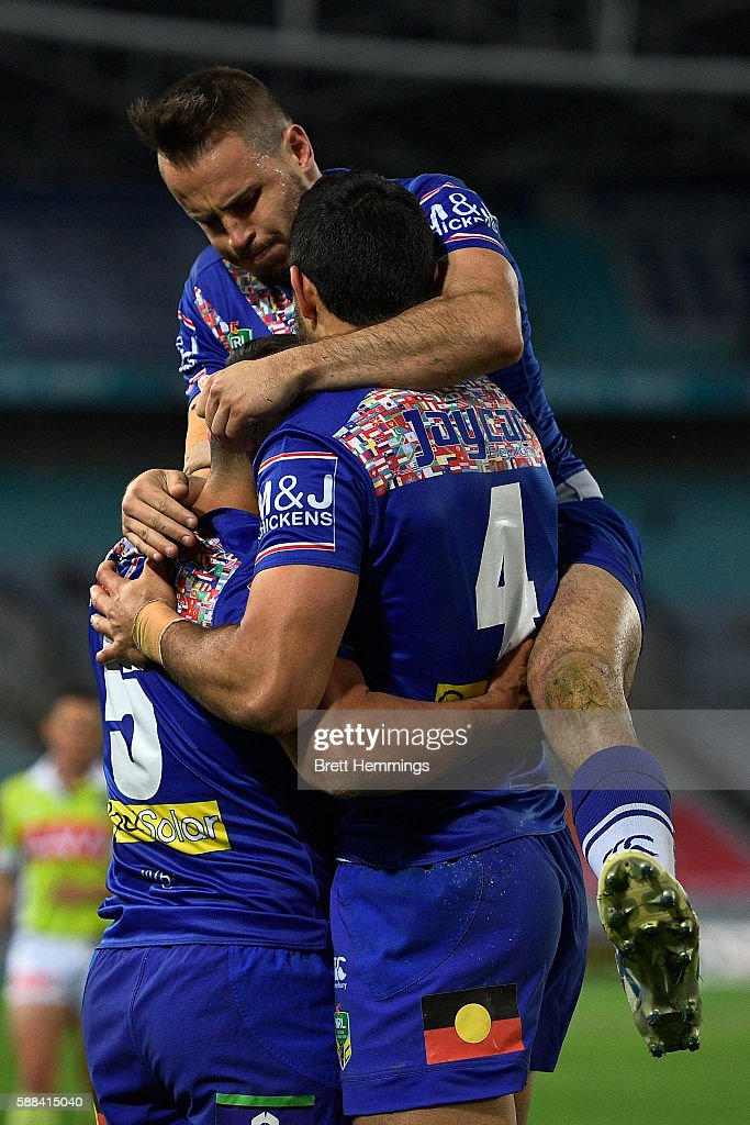 Sam Perrett of the Bulldogs celebrates with Curtis Rona and Josh Reynolds after scoring a try during the round 23 NRL match between the Canterbury Bulldogs and the Manly Sea Eagles at ANZ Stadium on August 11, 2016 in Sydney, Australia.