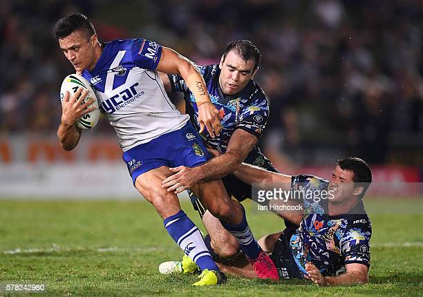 Sam Perrett of the Bulldogs is tackled by Kane Linnett and Lachlan Coote of the Cowboys during the round 20 NRL match between the North Queensland...