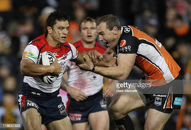 Sam Perrett of the Roosters is tackled by Gareth Ellis of the Tigers during the round 20 NRL match between the Wests Tigers and the Sydney Roosters...
