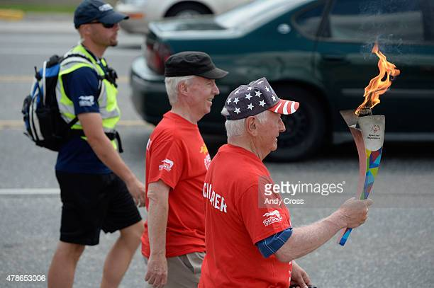 Sam Perry right walks with the Special Olympics Unified Relay Across America Flame of Hope along Parker Ave near Dartmouth St with Don Roth center...
