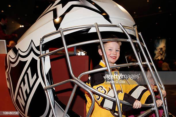 Sam Pollock the son of NHL referee Kevin Pollock pose inside a giant helmet inside the NHL Fan Fair part of 2011 NHL AllStar Weekend at the Raleigh...