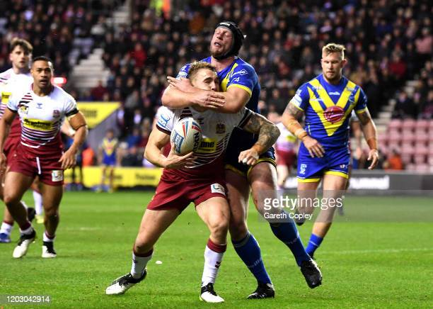 Sam Powell of Wigan scores a try as he is tackled by Chris Hill of Warrington leading to a red card during the Betfred Super League match between...