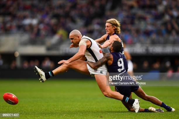 Sam PowellPepper of the Power is tackled by Bradley Hill and Stefan Giro of the Dockers during the 2018 AFL round 17 match between the Fremantle...
