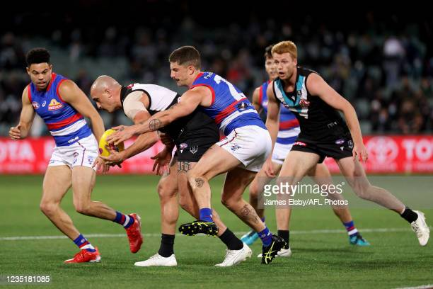 Sam Powell-Pepper of the Power is tackled by Tom Liberatore of the Bulldogs during the 2021 AFL Second Preliminary Final match between the Port...