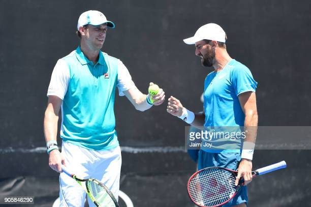 Sam Querrey of the United States and Steve Johnson of the United States talk tactics in their first round men's doubles match against Fernando...