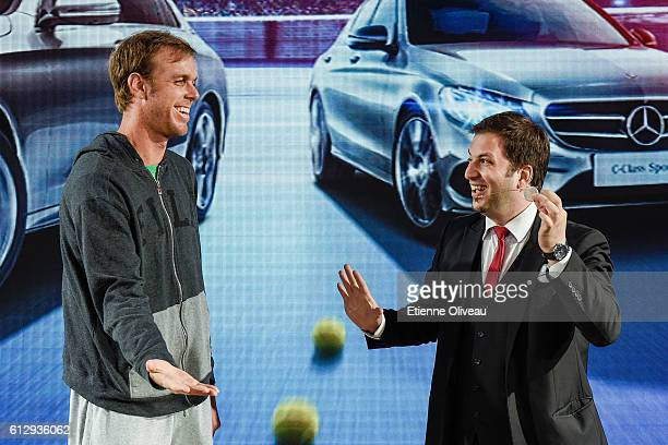 Sam Querrey of the United States participates in a magical trick during an event at the Mercedes booth on day six of the 2016 China Open at the China...