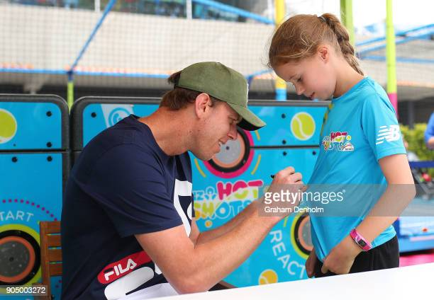 Sam Querrey of the United States signs his autograph for a young fan at Autograph Island during day one of the 2018 Australian Open at Melbourne Park...