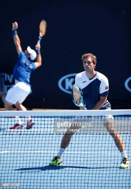 Sam Querrey of the United States stands at the net while Steve Johnson of the United States serves in their second round men's doubles match against...