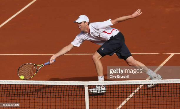 Sam Querrey of the United States stretches to play a forehand volley against Andy Murray of Great Britain during day three of the Davis Cup World...