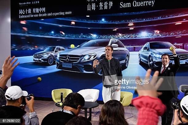 Sam Querrey of the United States throws balls to the audience during an event at the Mercedes booth on day six of the 2016 China Open at the China...