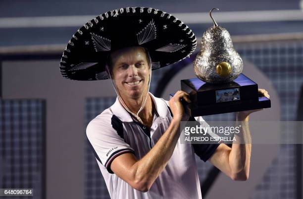 Sam Querrey of the US celebrates with the trophy after beating Rafael Nadal of Spain 63 76 in the ATP men's singles finals of the Mexican Tennis Open...