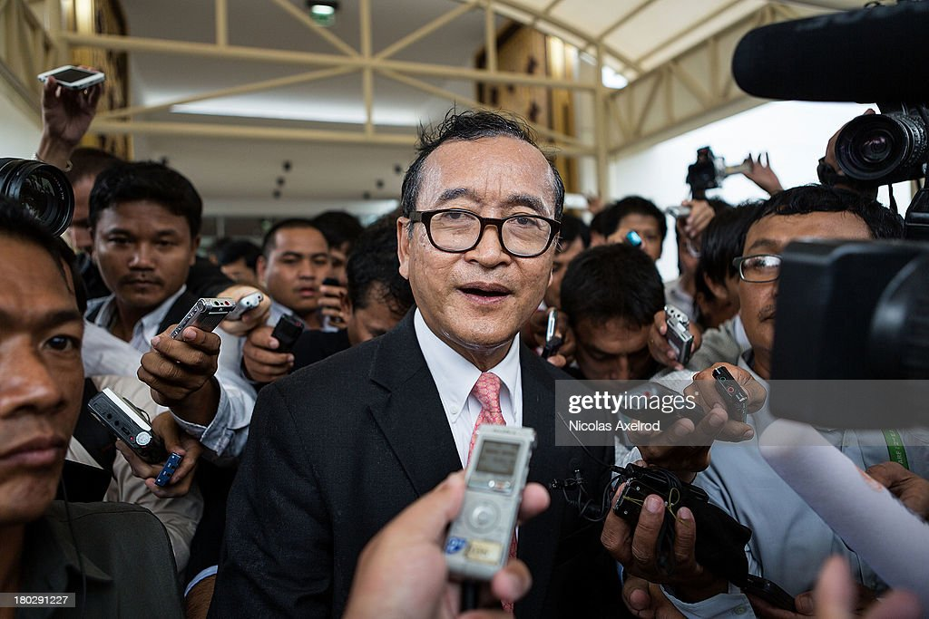 Sam Rainsy president of the Cambodia National Rescue Party talks to members of the press at the Phnom Penh airport after he welcomed King Norodom Sihamoni on his return to Cambodia on September 11, 2013 in Phnom Penh, Cambodia. King Norodom Sihamoni returns to Cambodia amid election controversy and has been asked by the opposition leader to intervene in the election dispute. The King had been in China where it is said he was receiving a medical check up.