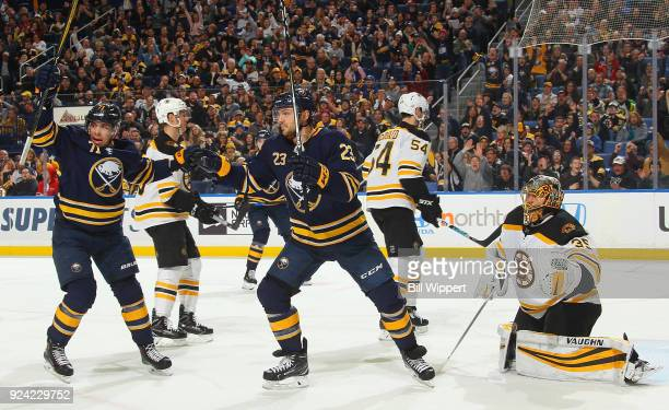 Sam Reinhart and Evan Rodrigues of the Buffalo Sabres react as Kyle Okposo scores a first period goal against Anton Khudobin of the Boston Bruins...