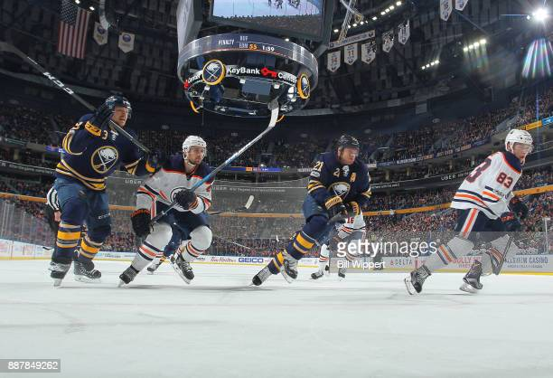 Sam Reinhart and Kyle Okposo of the Buffalo Sabres skate against Kris Russell and Matt Benning of the Edmonton Oilers during an NHL game on November...