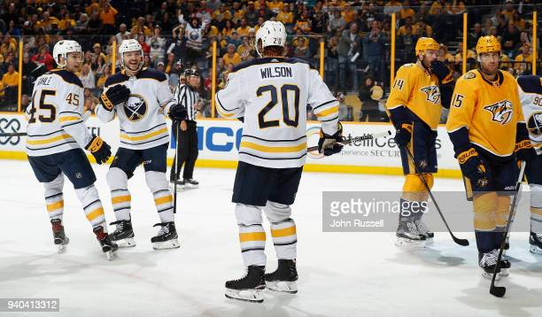 Sam Reinhart celebrates his goal with Brendan Guhle and Scott Wilson of the Buffalo Sabres against Craig Smith of the Nashville Predators during an...