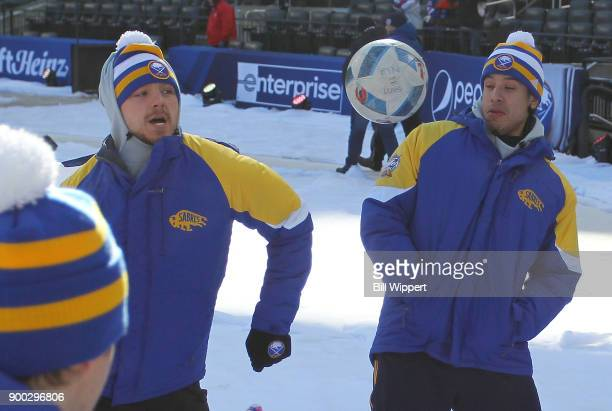 Sam Reinhart of the Buffalo Sabres chests a soccer ball as Jordan Nolan looks on prior to the 2018 Bridgestone NHL Winter Classic at Citi Field on...