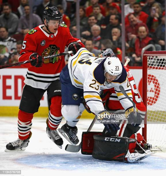 Sam Reinhart of the Buffalo Sabres falls over Corey Crawford of the Chicago Blackhawks as Connor Murphy defends at the United Center on March 07 2019...