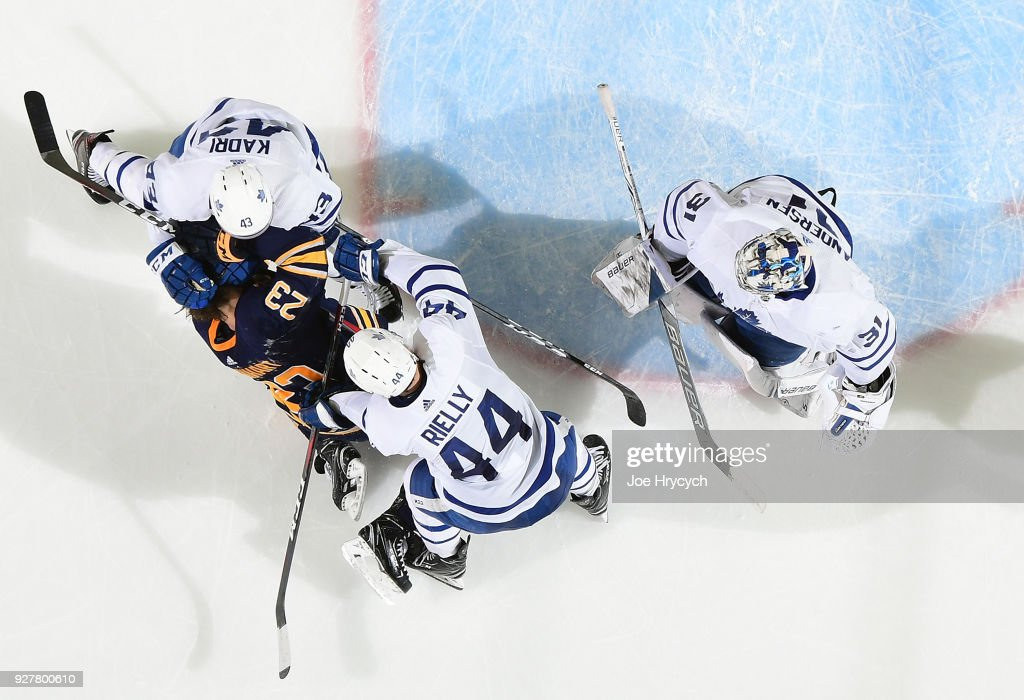 Sam Reinhart #23 of the Buffalo Sabres is roughed up by Nazem Kadri #43 and Morgan Rielly #44 of the Toronto Maple Leafs during an NHL game on March 5, 2018 at KeyBank Center in Buffalo, New York. Buffalo won, 5-3.