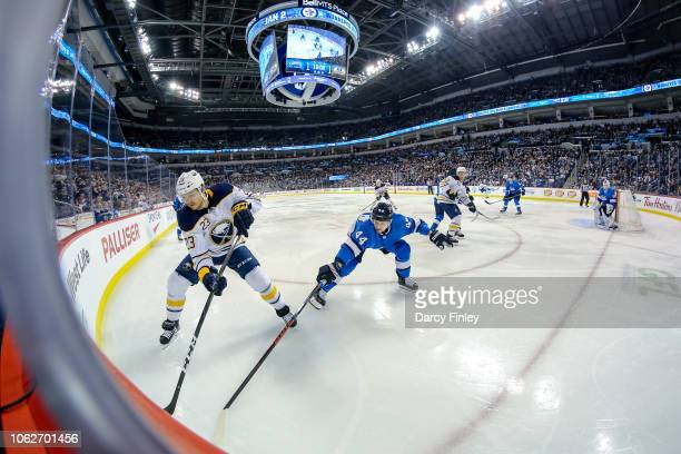 Sam Reinhart of the Buffalo Sabres plays the puck along the boards as Josh Morrissey of the Winnipeg Jets defends during third period action at the...