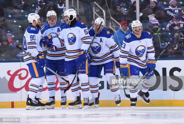 Sam Reinhart of the Buffalo Sabres skates toward the bench after celebrating his second period goal with teammates Ryan O'Reilly Jack Eichel Rasmus...