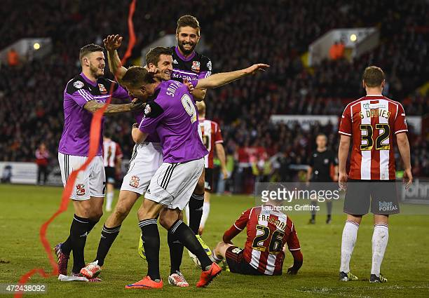 Sam Ricketts of Swindon Town is mobbed after the equalising goal during the Sky Bet League One playoff semi final match between Sheffield United and...